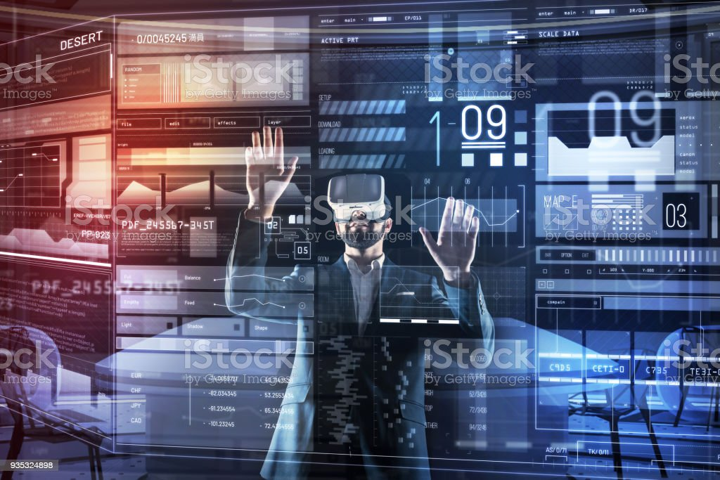 Qualified programmer feeling impressed while working in virtual reality glasses stock photo