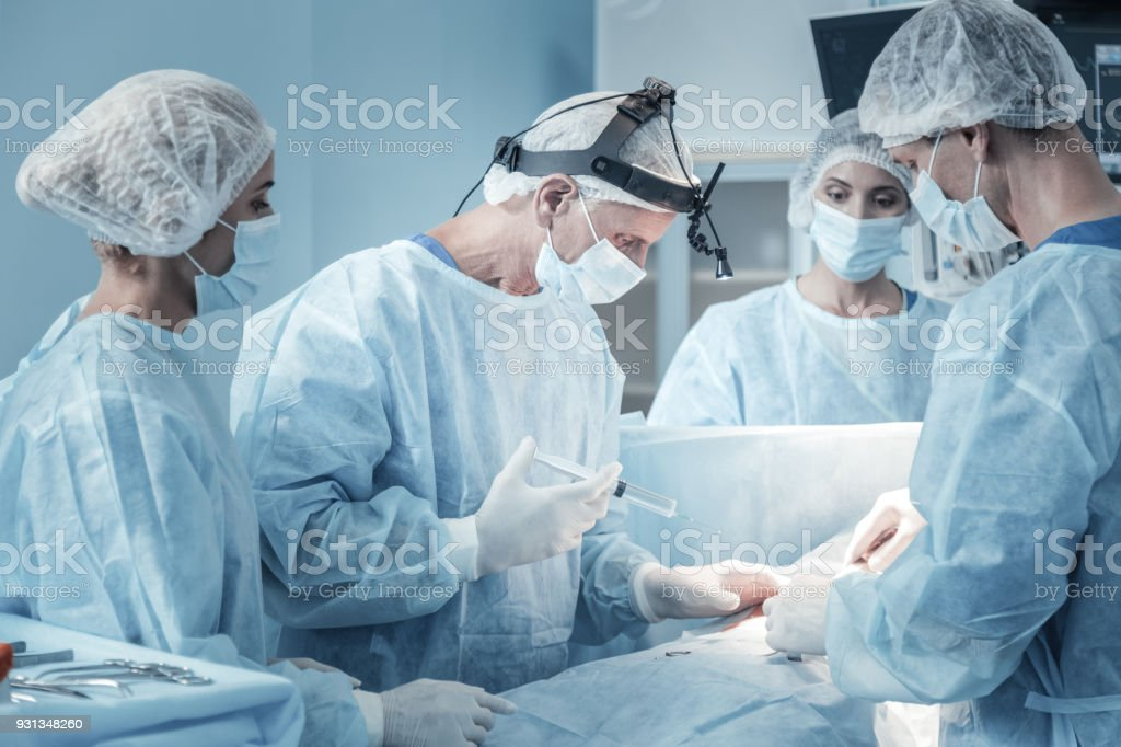 Qualified serious medic holding the syringe and making injection. stock photo