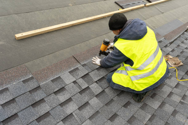 qualified workman in uniform work wear using air or pneumatic nail gun and installing asphalt or bitumen shingle on top of the new roof under construction residential building - installare foto e immagini stock
