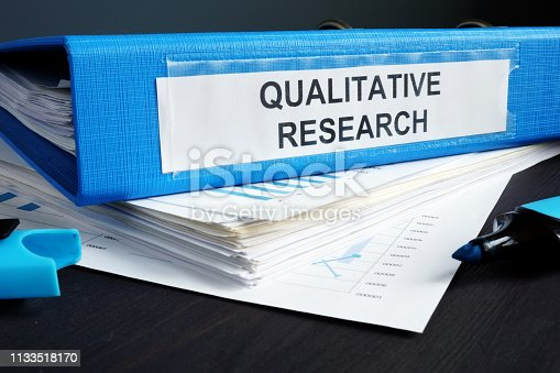 Qualitative research methods report in a blue folder.