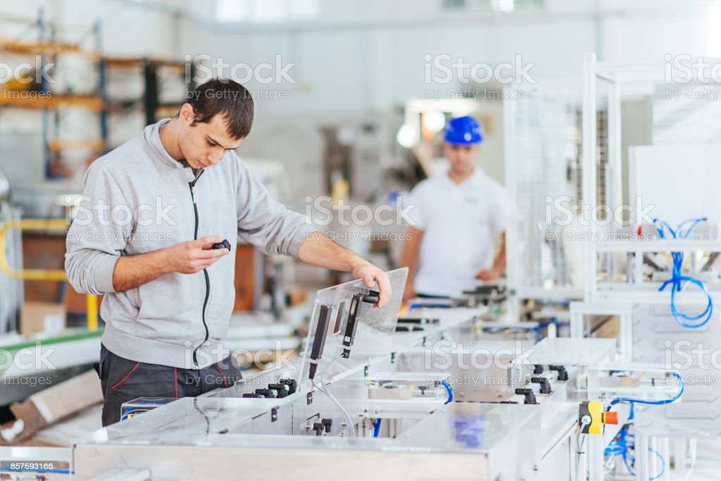 Engineers working on development of automated production line with...