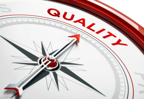 quality concept: arrow of a compass pointing quality text - quality control stock photos and pictures