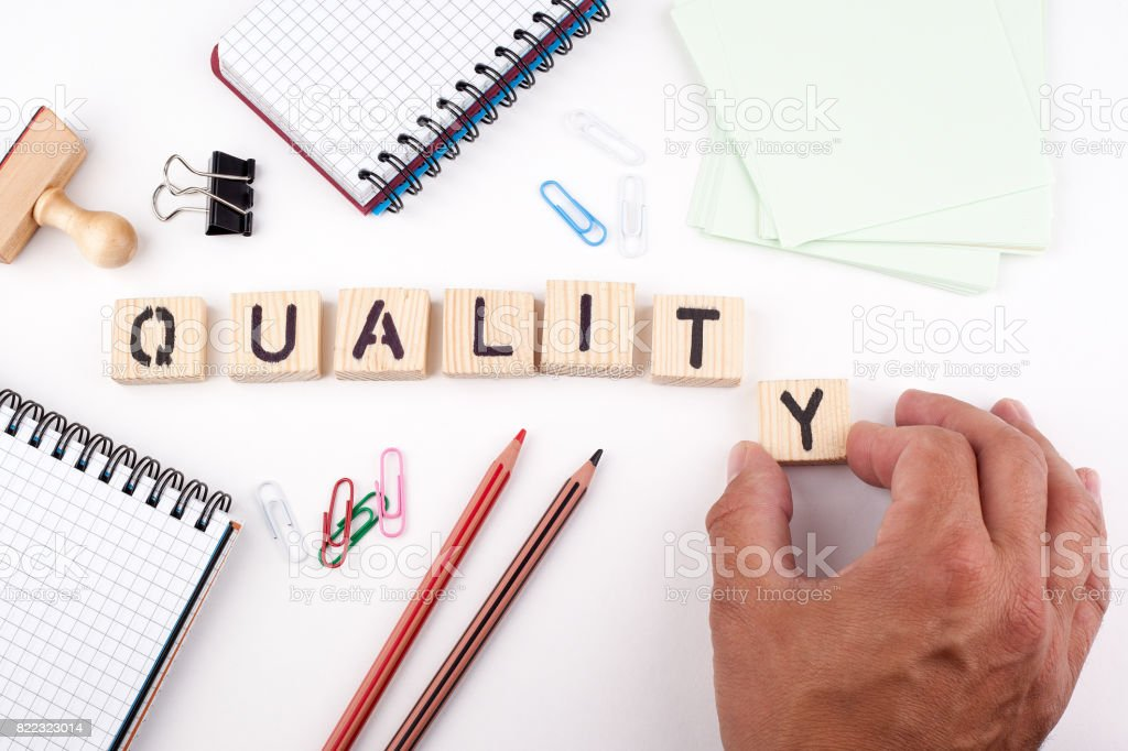 Quality concept. Wooden letters on a white background stock photo