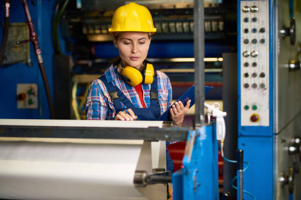 Quality Control at Modern Factory Portrait of beautiful woman checking machines  in modern factory working in quality control blotter stock pictures, royalty-free photos & images