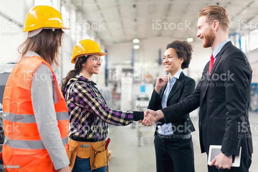 Quality control inspectors at the factory shaking hands with wor stock photo