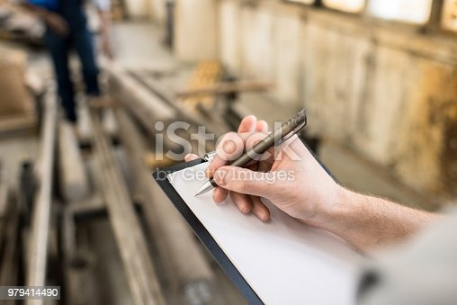 Close-up of unrecognizable quality control specialist holding clipboard with blank paper and writing information about production at plant