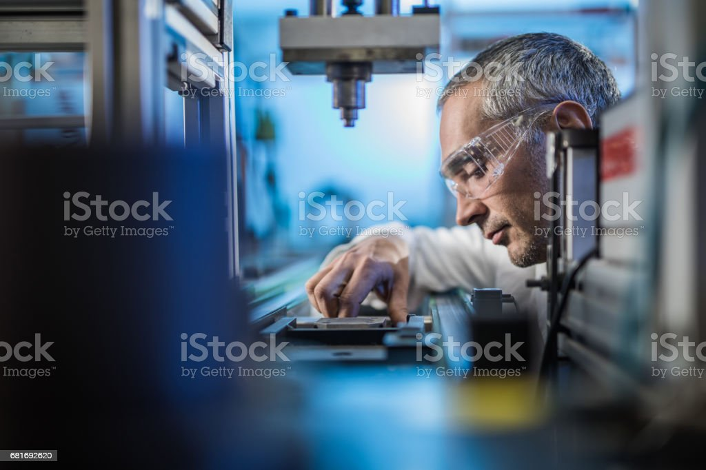 Quality control worker analyzing scientific experiment on a manufacturing machine. stock photo
