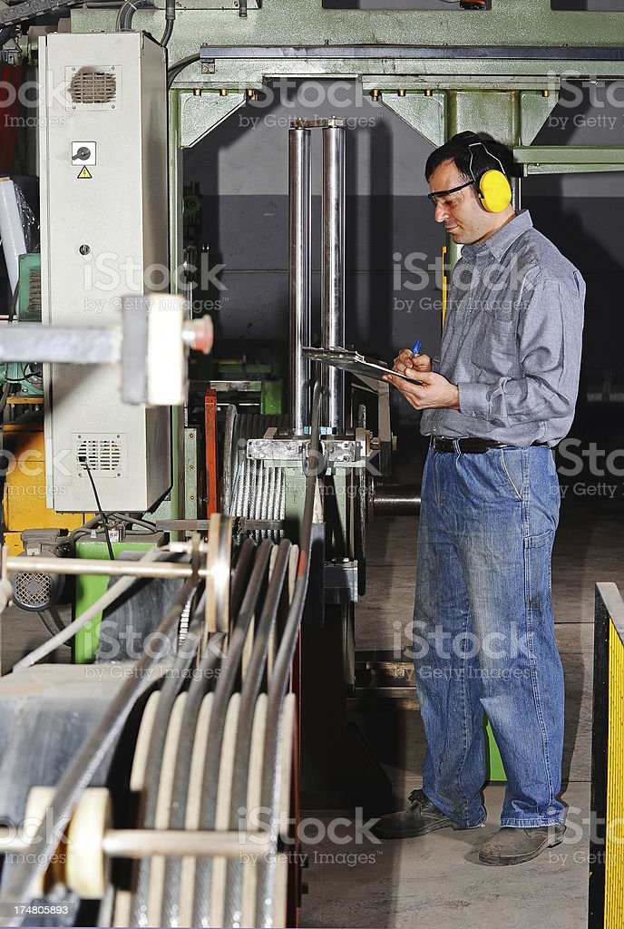 Quality control worker monitoring cable production stock photo