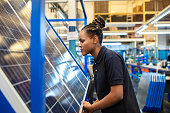 Side view of a female employee inspecting newly manufactured solar panels in company. Woman quality engineer examining solar panels in factory.