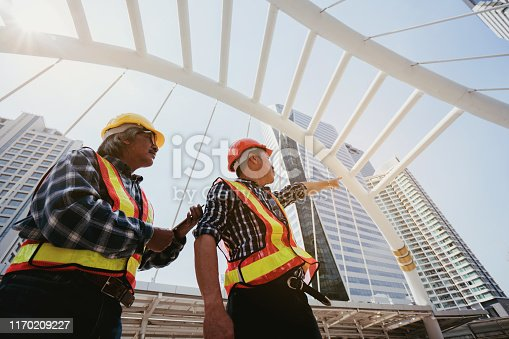 976560476 istock photo Quality engineers or construction teamwork. Safety concern for engineering or building work site or plant. Wearing helmet and protective equipment can safe workers life in industrial work or plant. 1170209227