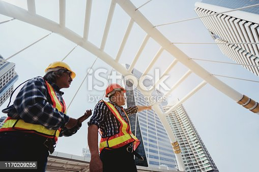 976560476 istock photo Quality engineers or construction teamwork. Safety concern for engineering or building work site or plant. Wearing helmet and protective equipment can safe workers life in industrial work or plant. 1170209255