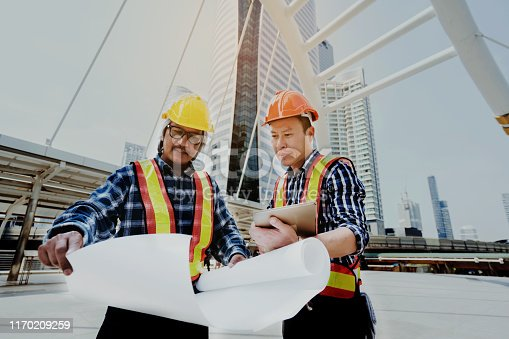 976560476 istock photo Quality engineers or construction teamwork. Safety concern for engineering or building work site or plant. Wearing helmet and protective equipment can safe workers life in industrial work or plant. 1170209259