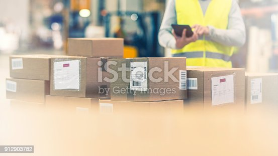 Unrecognizable quality inspector in a reflective vest with a digital tablet examining a stack of boxes in a warehouse.