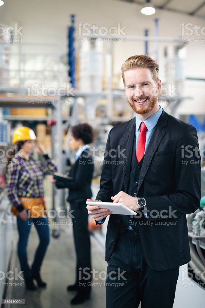 Quality inspector using tablet pc and smiling stock photo