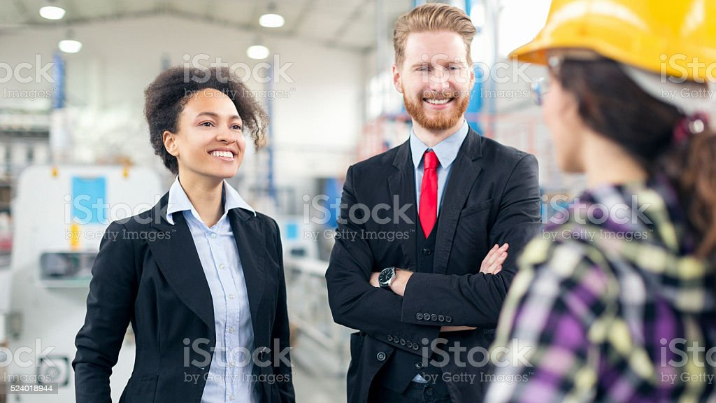 Quality inspectors in the factory talking to workers stock photo