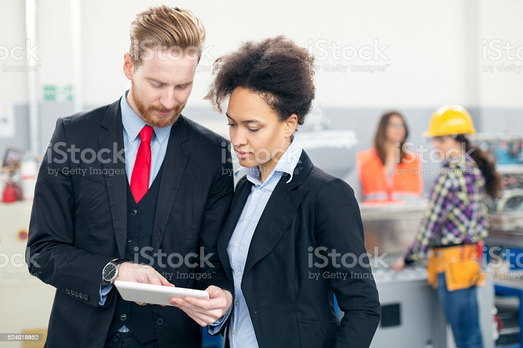 Quality inspectors in the factory using tablet pc stock photo