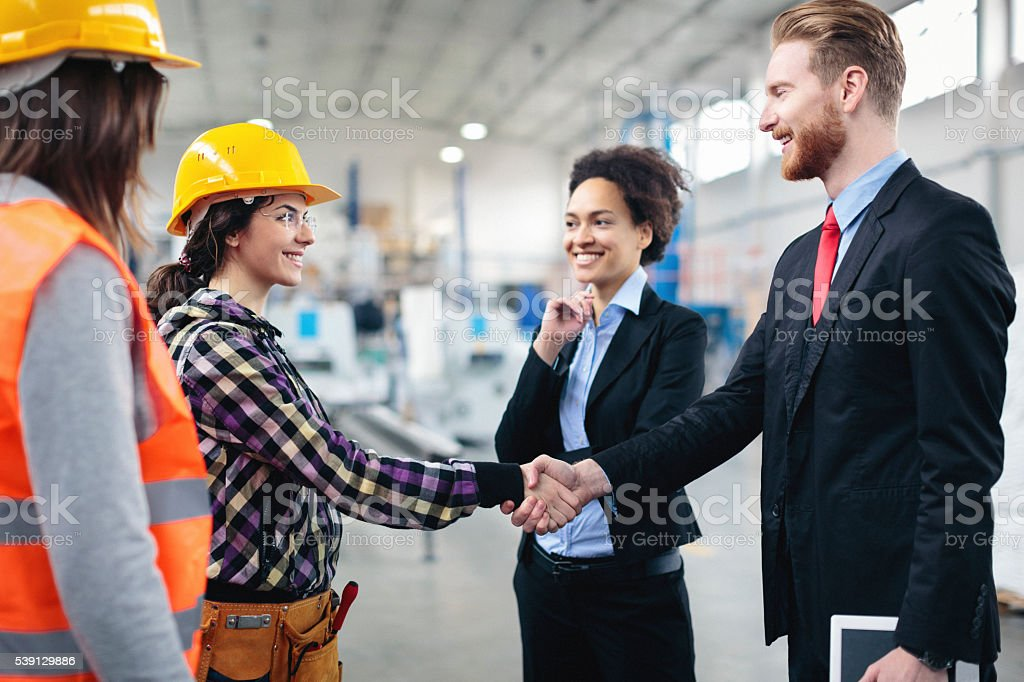 Quality inspectors shaking hands with workers stock photo