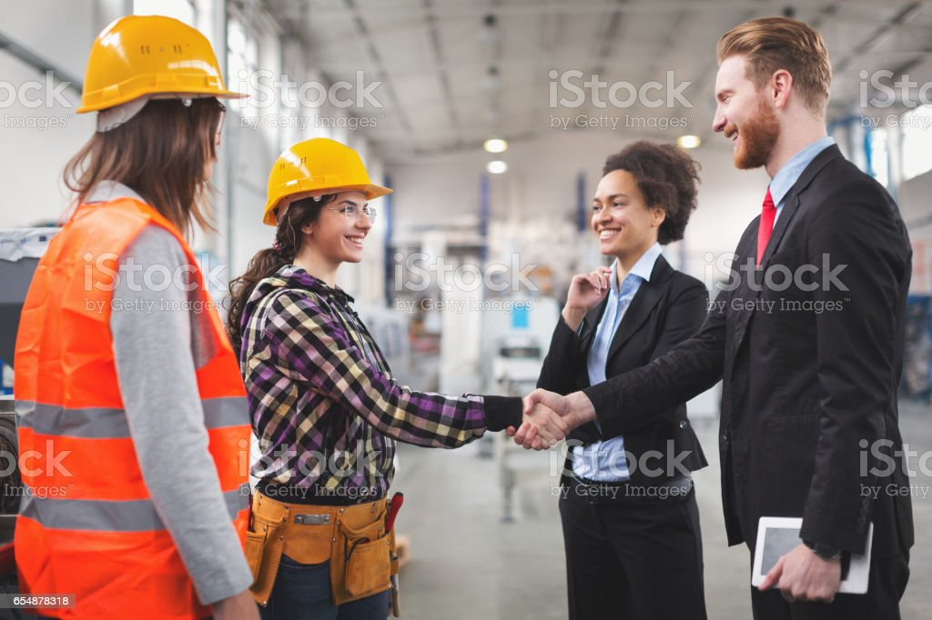 Quality inspectors shaking hands with workes in factory stock photo