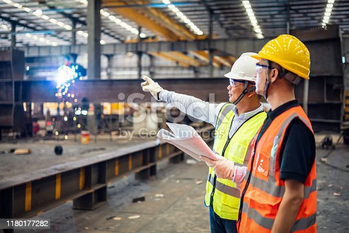 Quality inspectors working in a steel factory.