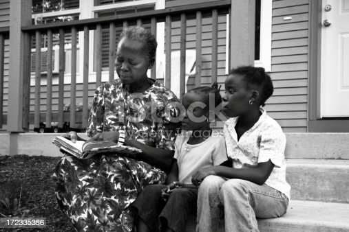 African grandma reads to her two granddaughters (shot in b/w)
