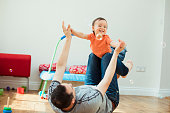 An adorable mixed-race boy is being held up into the air by his father as he laughs with happiness.