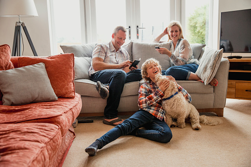 A teenage boy plays with the family dog on the floor whilst his parents sit on the sofa.
