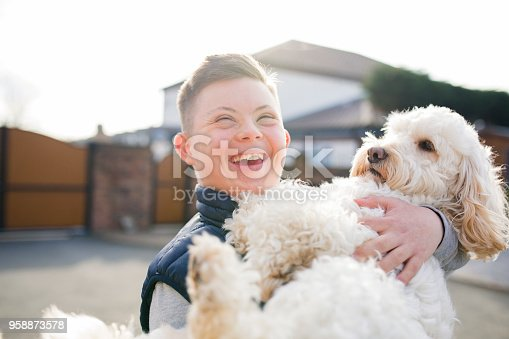 A boy with down syndrome hugs his pet dog in the driveway.