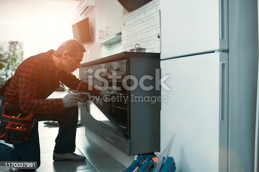 Portrait of mature man wearing tool kit standing in the kitchen, holding a screwdriver and fixing the oven door. Horizontal shot. Side view