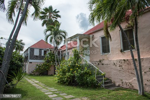 Christiansted, St. Croix, VI-October 22,2019: Old pink residential buildings with brick details and tropical palm trees in downtown Christiansted, VI
