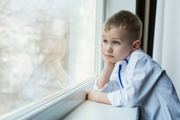quarantine, a boy looks out the window quarantine, a boy looks out the window lockdown stock pictures, royalty-free photos & images