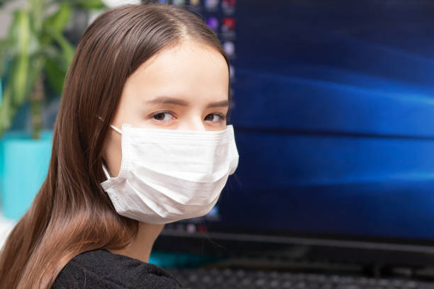 Quarantine and coronavirus danger. A girl in an antibacterial mask works at a computer stock photo