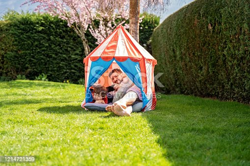 Quarantine and self isolation during coronavirus pandemic period concept. Humour and positive attitude. Man with little son sitting in child tent outdoors in garden at home