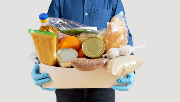 Quarantine donation box. Food, clothing and personal protective equipment Mens hands hold Quarantine donation box. Food, clothing and personal protective equipment. Food delivery concept. charitable donation stock pictures, royalty-free photos & images