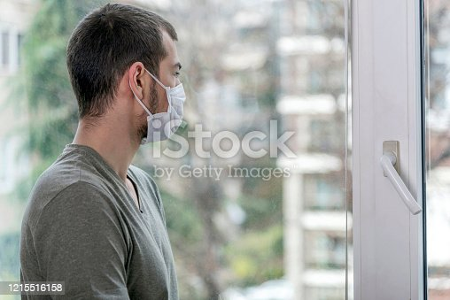 Caucasian worried one young adult man looking out the window using a surgical mask and glove in Turkey. COVID-19