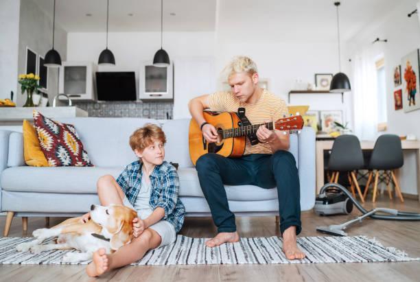 Tiempo de la familia en cuarentena: Hermanos pequeños y mayores en la sala de estar juntos. Adolescente tocando la guitarra acústica, sonriendo niño jugando con su perro beagle en el suelo. Concepto de valores de familia o de hogar - foto de stock