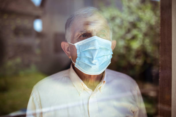 Quarantine for old people Senior man stays home because of Corona virus. He stands by the window and looks out at the garden. quarantine stock pictures, royalty-free photos & images