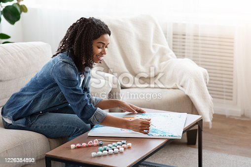 Quarantine Hobby. Relaxed Black Woman Drawing Painting By Numbers, Sitting On Couch At Home