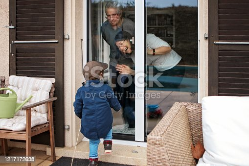 Quarantine, self isolation and social distancing during coronavirus pandemic. Old senior grandparents couple communicate to grandson through closed window. Lockdown