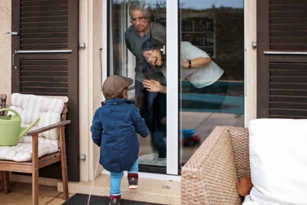 quarantine, self isolation and social distancing during coronavirus pandemic. old senior grandparents couple communicate to grandson through closed window. lockdown - visita foto e immagini stock