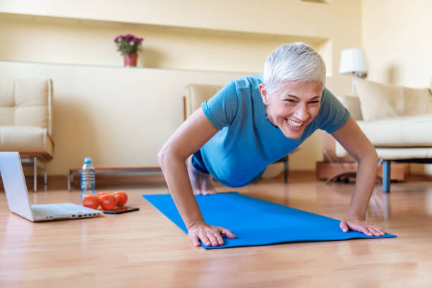 Quarantine. Senior woman exercising in home gym. Beautiful senior woman doing stretching exercise while sitting on yoga mat at home. Mature woman exercising in sportswear by stretching forward to touch toes. Healthy active lady doing yoga. eastern european descent stock pictures, royalty-free photos & images