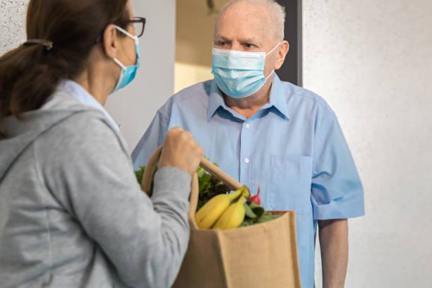 Quarantine – woman helping senior man stock photo