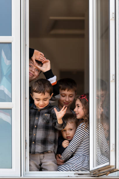 quarantined family photographed through window - quarantined family stock pictures, royalty-free photos & images