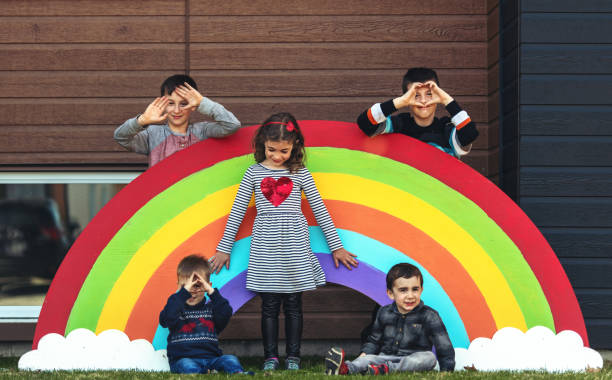 quarantined family posing in front of a giant rainbow - quarantined family stock pictures, royalty-free photos & images