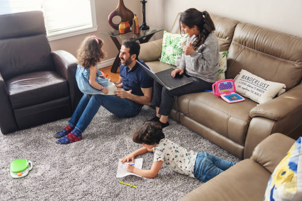 Quarantined family telecommuting with kids du to the covid-19 stock photo