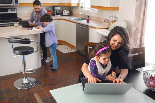 Quarantined family telecommuting with kids stock photo