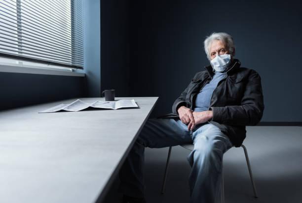 Unter Quarantäne Senior sitzen zu Hause allein mit chirurgischer Maske – Foto