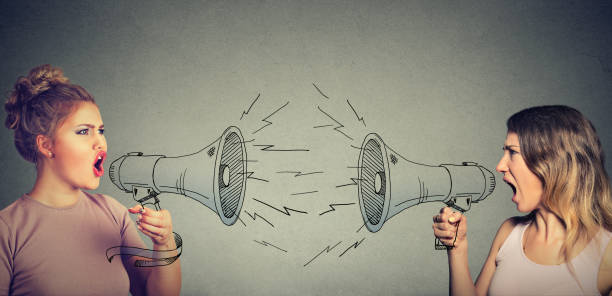 Quarrel between two women screaming at each other in megaphone stock photo