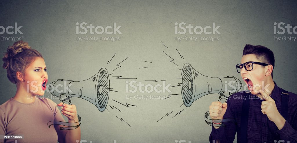 Quarrel between woman and man screaming at each other in megaphone stock photo