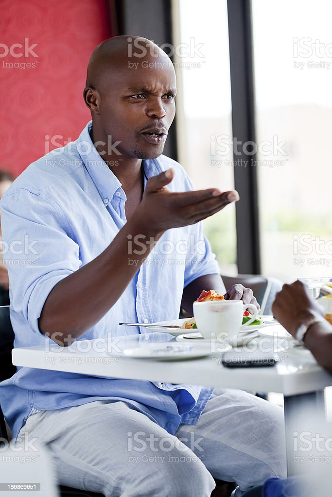 Quarrel during meeting A disappointed african man arguing with his friend during lunch. Adult Stock Photo