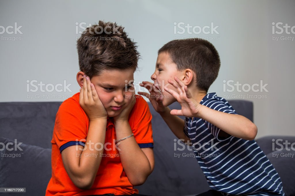 Quarreling kids - boy shouting at his brother. Child shouting loud. little child boy holding hands near head and scares his brother Quarreling kids - boy shouting at his brother Aggression Stock Photo